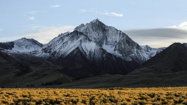 Sierra Nevada snowy mountain range and grassy plains at sunset